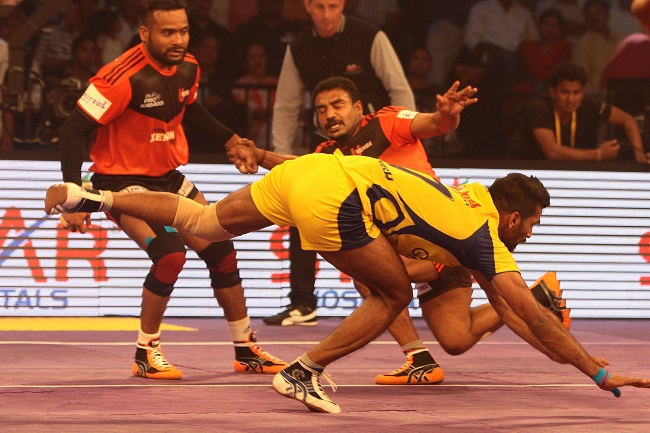 Sukesh Hegde of Telugu Titan escapes from the clutches of U Mumba defenders Jeeva Kumar and Vishal Mane who in the background looking on in the Star Sports Pro Kabaddi season 3 opener