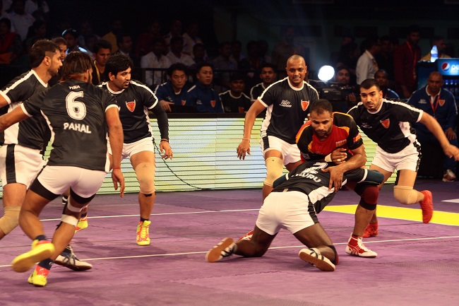 Rajaguru Subramanian the ace defender of Dabang Delhi goes down and attempts a double thy hold on rival Skipper Surjeet Narwal of Bengaluru Bulls on the inaugural day of Star Sports Pro Kabaddi Season 3