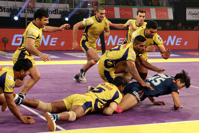 Jang Kun Lee of Bengal Warriors trying to escape from the hold applied by Dharamaraj Cheralathan and Sukesh Hegde of Telugu Titans