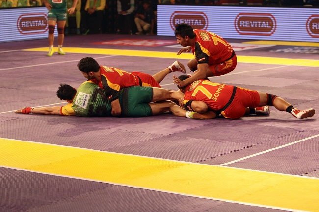 Patna Pirates new find Rohit Kumar uses his agility and power to wriggle out of the ankle hold affected by Bengaluru Bulls Somvir (70) & Shrikant Tewthia in Match No. 8 of the Star Sports Pro Kabaddi