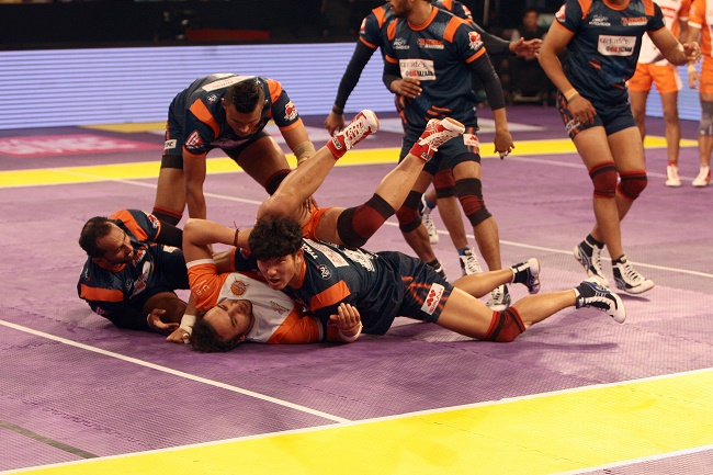 Captain of the Puneri Paltan Manjeet Chhillar is piled onto by the defense of the Bengal Warriors in the Star Sport Pro Kabaddi season 3 in Mumbai