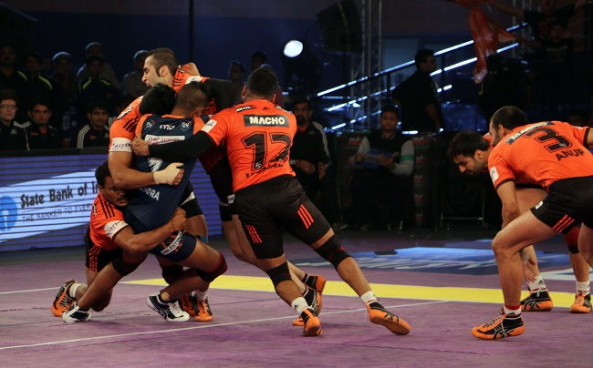 Mahendra Rajput is caught by Fazel Atrachali of U Mumba and then surrounded by the U Mumba defense in the second semi final of the Star Sports Pro Kabaddi season 3 in Delhi