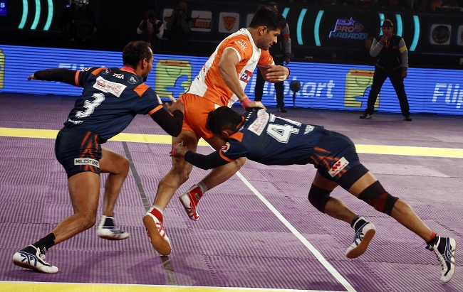 Deepak Hooda escapes the tackles of Bengal defenders Bajirao Hodage and Umesh Mhatre in the 3rd place match of the Star Sports Pro Kabaddi season 3 in Delhi